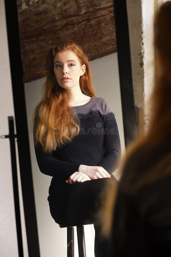 Röd Haired kvinna i den svarta klänningen som ser henne i en spegel arkivbild