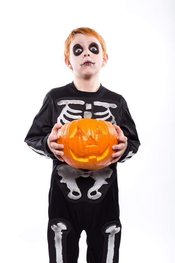 Röd haired pojke i den skelett- dräkten som rymmer en pumpa halloween royaltyfria bilder