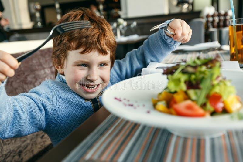 Röd haired pojke med gafflar som äter sallad royaltyfri fotografi