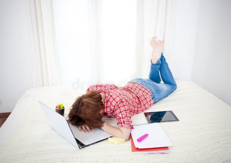 Röd haired studentalseep på bärbara datorn, medan studing arkivbilder