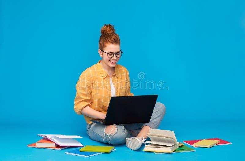Röd haired tonårs- studentflicka med bärbara datorn royaltyfri foto