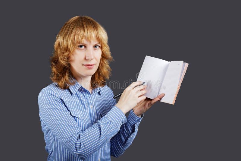 Röd haired ung kvinna som rymmer en öppen anteckningsbok royaltyfri fotografi