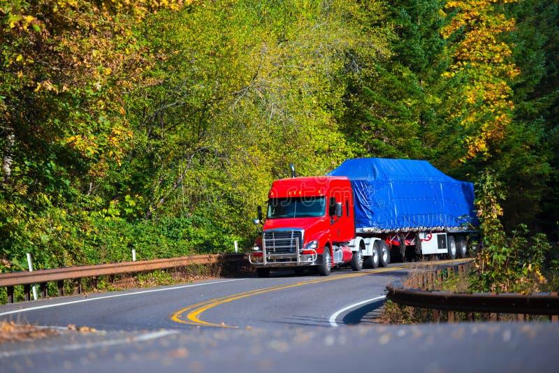 Röd halv släp för plan säng för lastbil på den slingriga hösthuvudvägen arkivbild