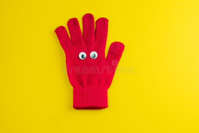 röd handske med googly ögon som isoleras på en gul bakgrund royaltyfri bild