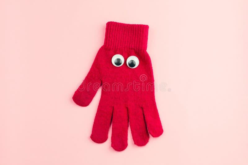 röd handske med googly ögon som isoleras på en rosa bakgrund royaltyfri bild