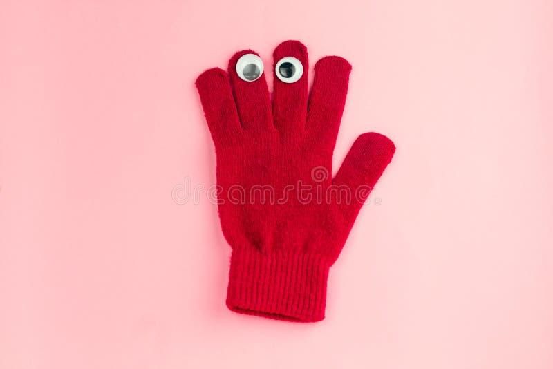 röd handske med googly ögon som isoleras på en rosa bakgrund royaltyfri fotografi
