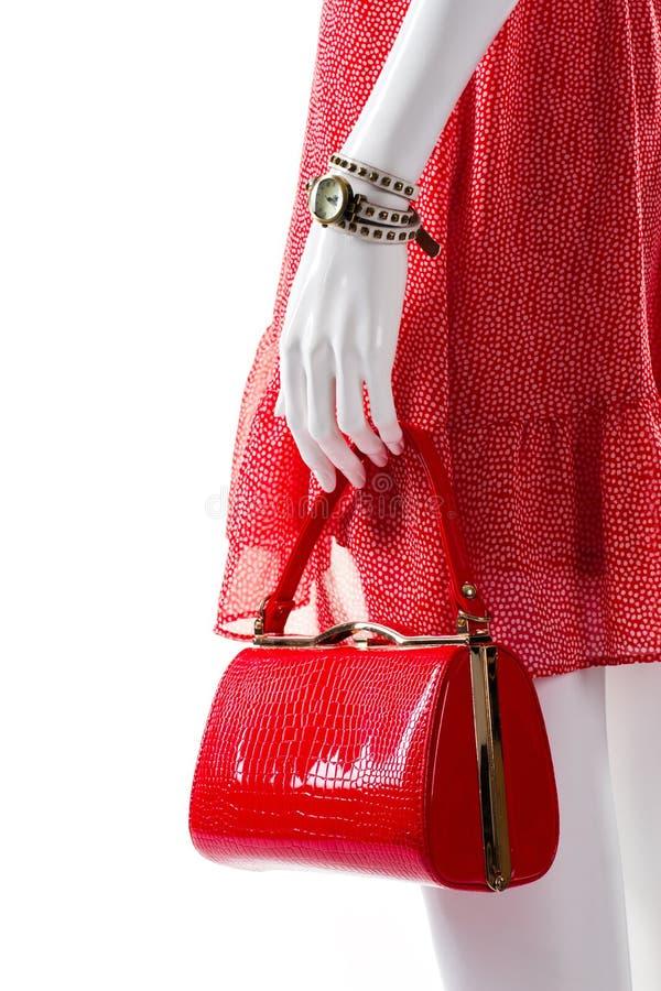 Röd handväska i skyltdockas hand arkivbild