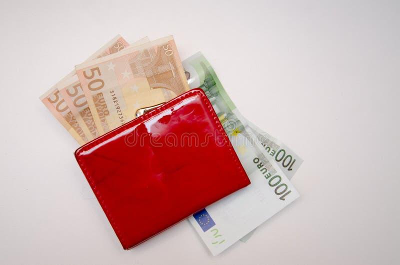 Röd handväska med pengar på en vit bakgrund royaltyfri foto