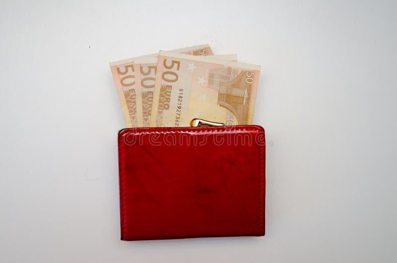 Röd handväska med pengar på en vit bakgrund fotografering för bildbyråer