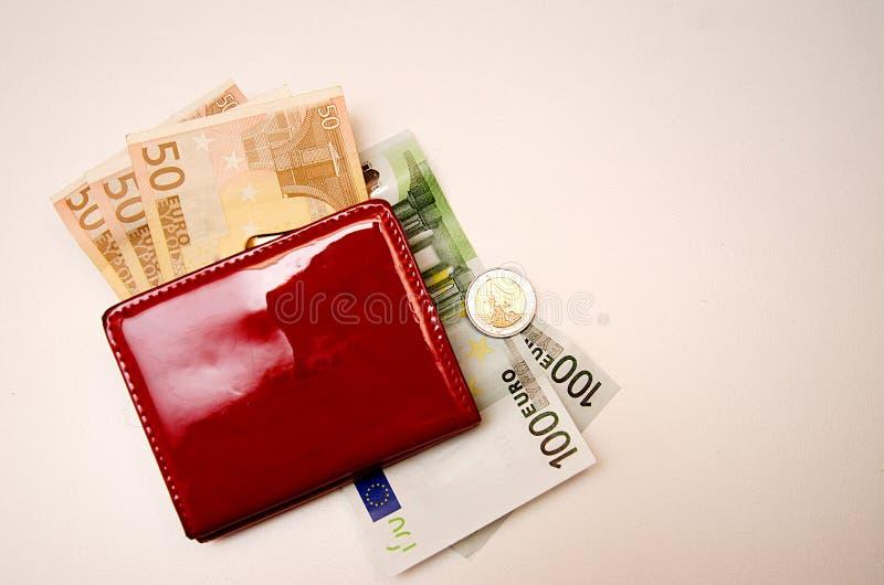 Röd handväska med pengar på en vit bakgrund arkivbild