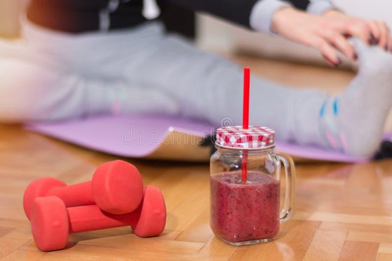 Röd hantel och smoothie i retro krus på golv och kvinnan som arbetar sträcka övningar arkivfoton