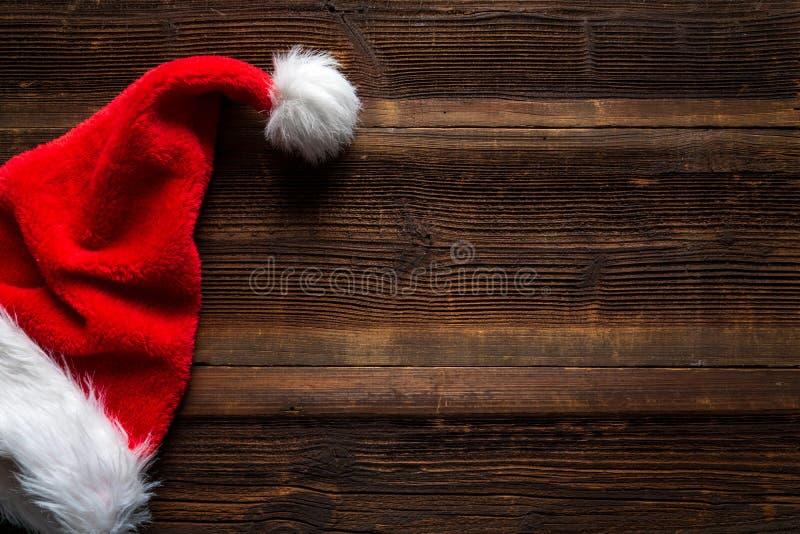Röd hatt för jultomten på träbakgrund, feriejulbegrepp royaltyfri foto