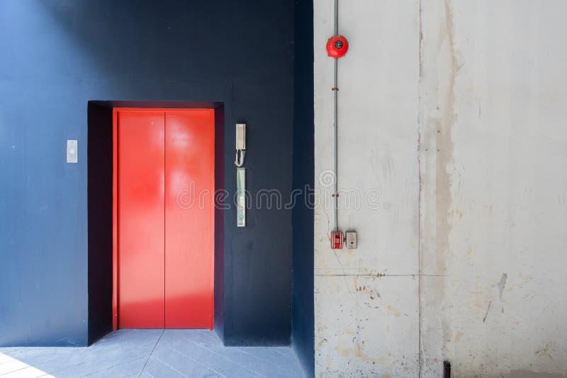 Röd hiss och svart vägg med brandlarmet, telefon royaltyfri foto