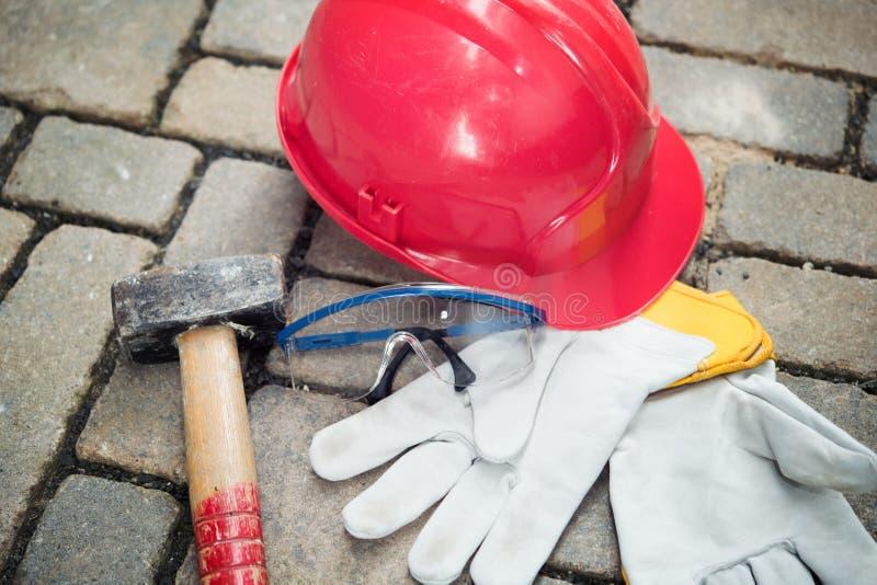 Röd hjälm, skyddsglasögon, hammare och arbetshandskar royaltyfri fotografi
