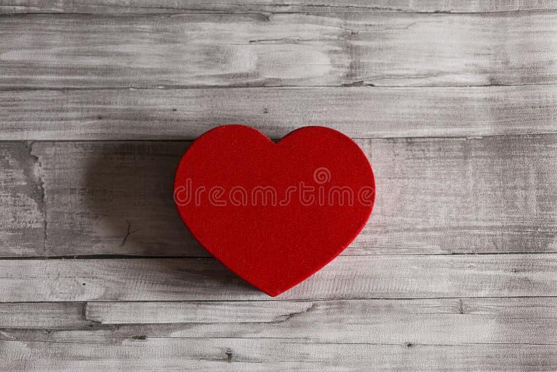 Röd hjärta över grå träbakgrund som isoleras hj?rta f?r g?van f?r dagen f?r begreppet f?r den bl?a asken f?r bakgrund isolerade b royaltyfri fotografi