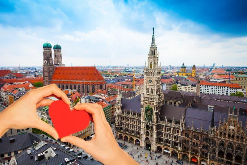 Röd hjärta för handhåll över Neues Rathaus i Munich royaltyfria foton