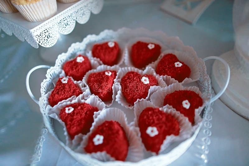 Röd hjärta för kakavalentin` s på en vit platta för snöra åt som gifta sig variationsefterrättkakor med smaklig bufféfärg som dek royaltyfria bilder