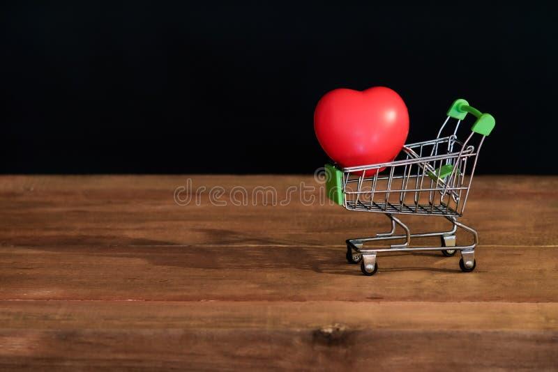 Röd hjärta för stilleben på shoppingvagnen på trä royaltyfria foton