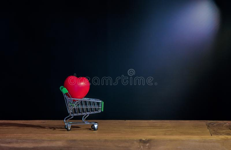 Röd hjärta för stilleben på shoppingvagnen på trä royaltyfri bild