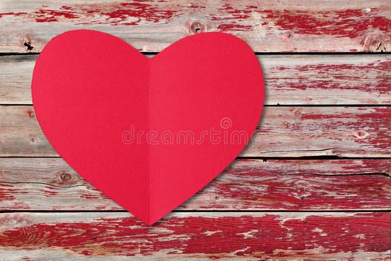 Röd hjärta för valentindagpapper över en åldrig wood bakgrund royaltyfria foton