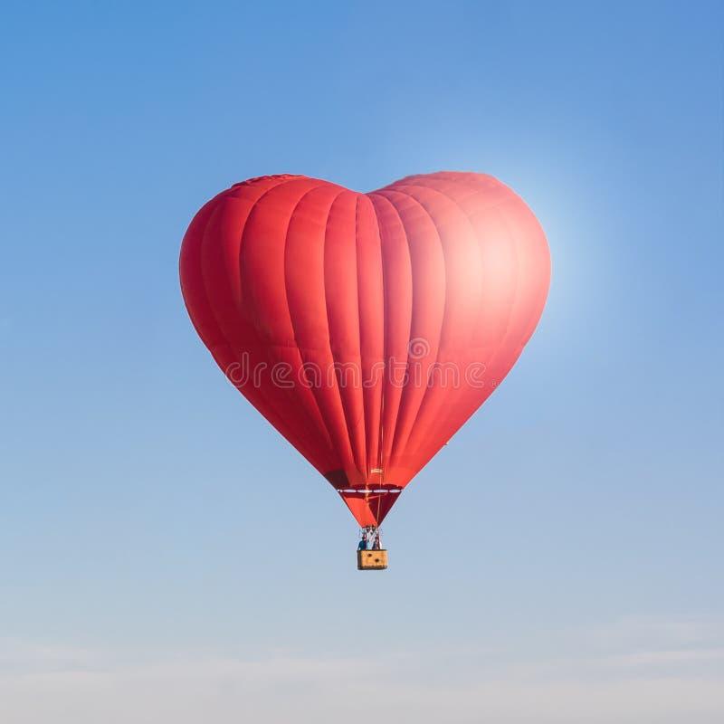Röd hjärta formad luftballon som isoleras i himlen royaltyfri foto