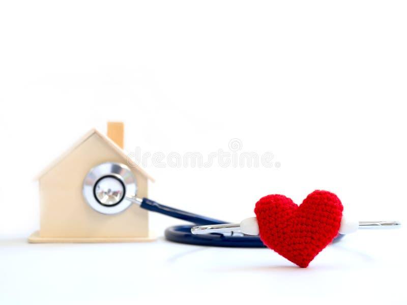 Röd hjärta genom att använda stetoskopet på den blåa bakgrunden för vård- kontroll för hus Begrepp av förälskelse och att att bry arkivfoto