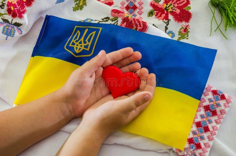 Röd hjärta i barns händer på bakgrunden av den ukrainska flaggan och den broderade skjortan arkivbild