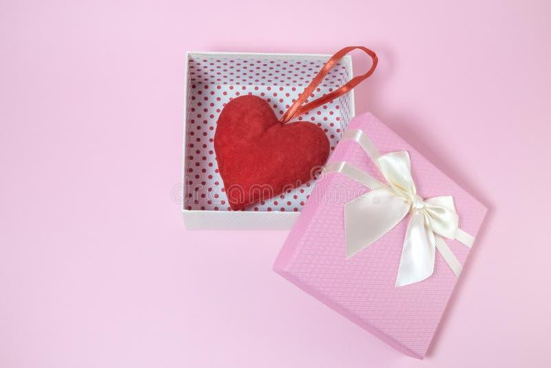 Röd hjärta i den rosa gåvaasken på den rosa bakgrunden royaltyfri bild