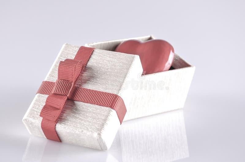Röd hjärta i en öppnad gåvaask på vit med reflexion arkivbild