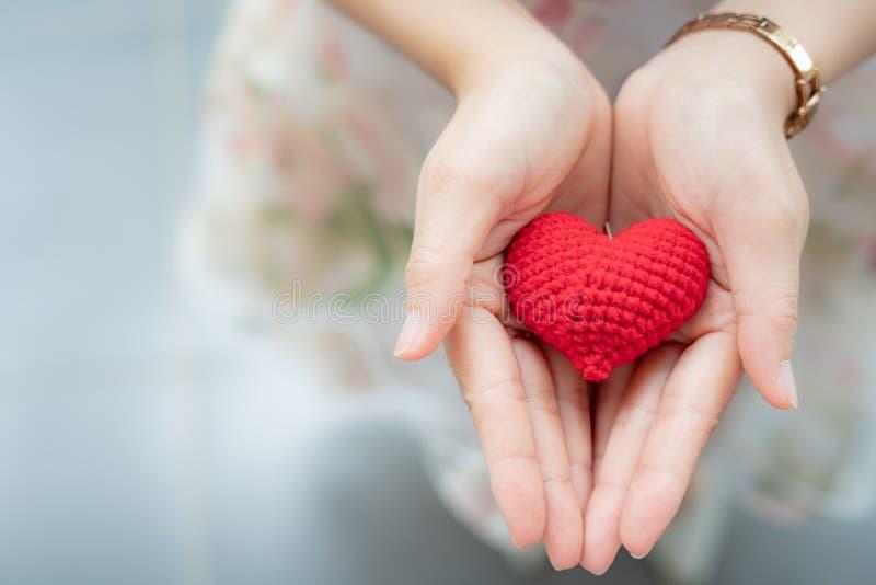 Röd hjärta i händer från över Gör, sunt förälskelse, donationorgan arkivbild