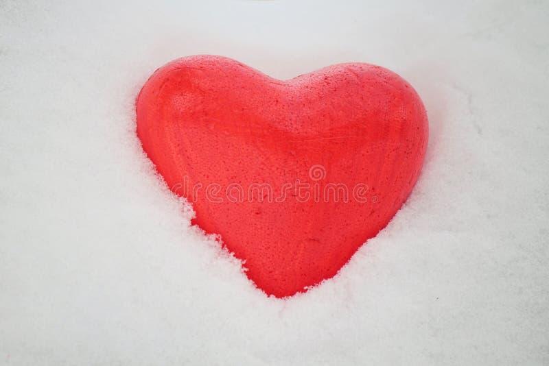 Röd hjärta i snön arkivfoton