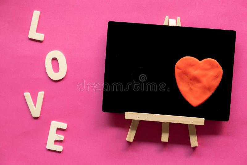 röd hjärta i svart tavla och ord FÖRÄLSKELSE på rosa bakgrund, förälskelsesymbol, valentin dag royaltyfri fotografi