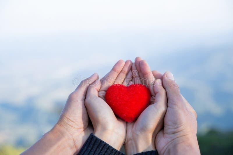 Röd hjärta i vänparhänder på suddighetsbakgrund av naturen arkivbilder