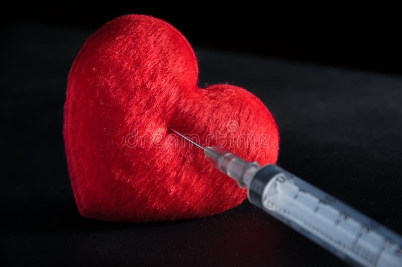 Röd hjärta med injektionssprutan fotografering för bildbyråer