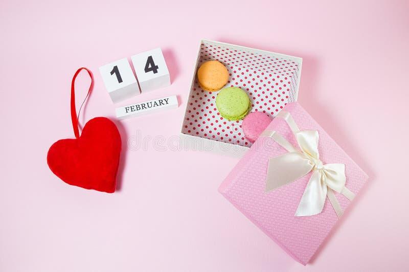 Röd hjärta med träkalendern och macarons i den rosa gåvaasken royaltyfri foto