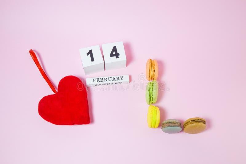Röd hjärta med träkalendern och macarons i form av bokstäver L simbol av förälskelse fotografering för bildbyråer