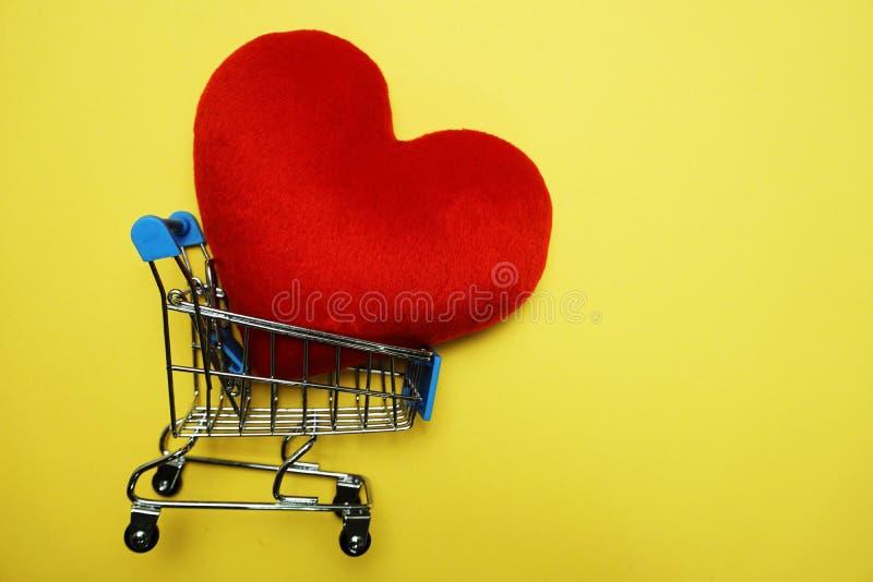 Röd hjärta och Mini Trolley Shopping Cart på gul bakgrund arkivbild