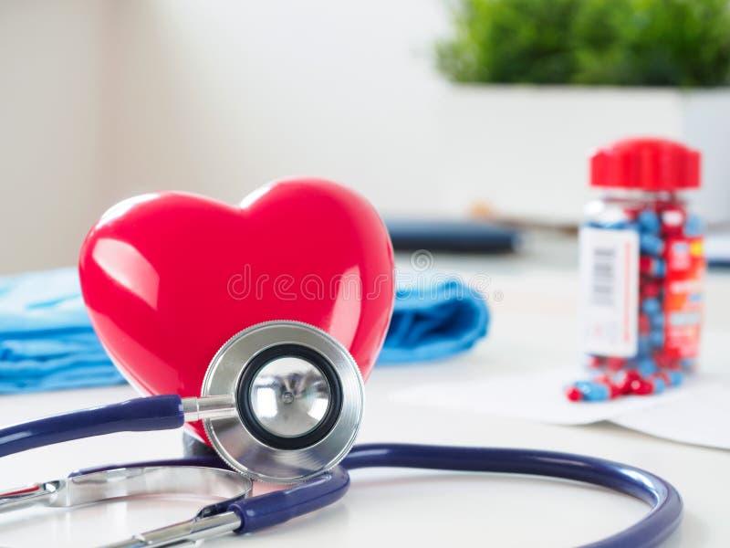 Röd hjärta och stetoskop på doktorstabellen fotografering för bildbyråer