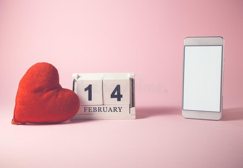 Röd hjärta och träkalender och smartphone med den tomma skärmen royaltyfria bilder