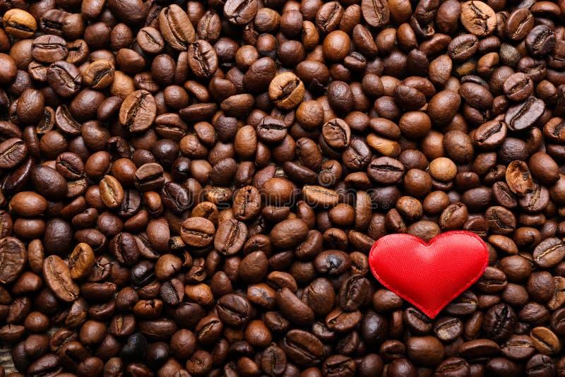 Röd hjärta på bakgrund för kaffebönor arkivbild