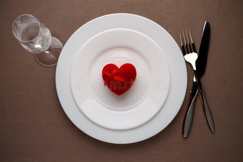 Röd hjärta på en platta för romantiskt datum på valentindag fotografering för bildbyråer