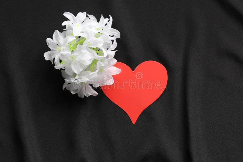 Röd hjärta på en svart bakgrund och vita blommor arkivfoton