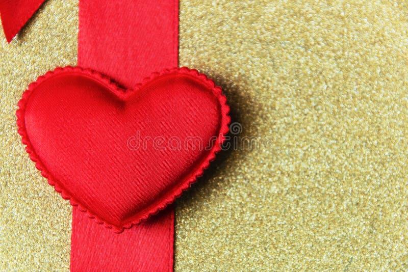 Röd hjärta på ett rött band och den guld- bakgrunden arkivbild