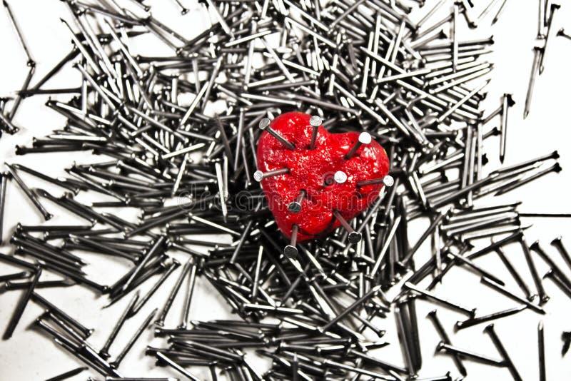 Röd hjärta på högen av järngrå färger spikar, trängt igenom av a spikar royaltyfria bilder