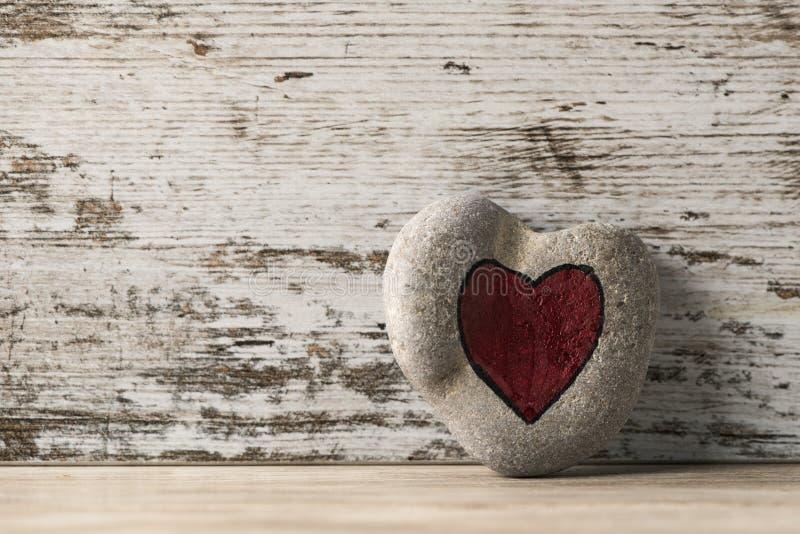Röd hjärta som dras på en sten royaltyfria bilder