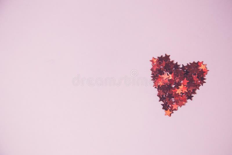 Röd hjärta som göras av konfettier i form av den röda stjärnan, på rosa backgro royaltyfri fotografi