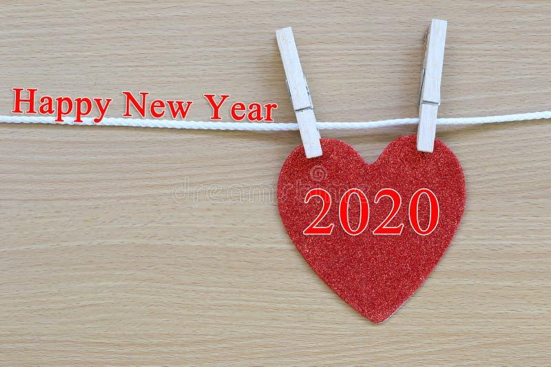 Röd hjärta som hänger på ett rep och, har text för lyckligt nytt år royaltyfri fotografi