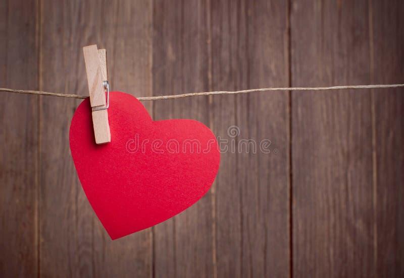 Röd hjärta som hänger på klädstrecket royaltyfri foto