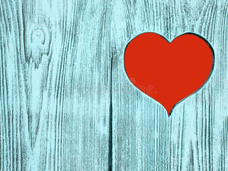 Röd hjärta som snidas i ett träbräde Bakgrund royaltyfri foto
