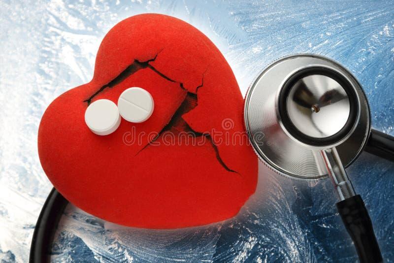 Röd hjärta, stetoskop och preventivpillerar arkivfoto